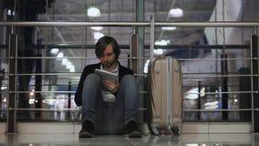 飞行运输、延迟,沮丧的人有他的行李和片剂的,头疼和红色眼睛的问题 股票录像