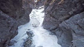飞行通过与下面河的一个积雪的峡谷:原始冬天风景和雪 在岩石的飞行和 股票视频