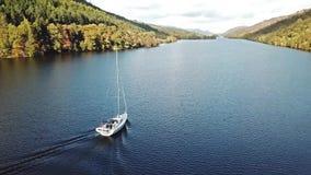 飞行通过在海湾Oich上的伟大的幽谷往在一条白色马达游艇后的奈斯湖在苏格兰高地- 股票录像