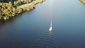 飞行通过在海湾Oich上的伟大的幽谷往在一条白色马达游艇后的奈斯湖在苏格兰高地- 股票视频