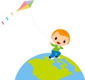 飞行风筝的一个逗人喜爱的男孩 免版税库存图片