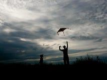 飞行风筝的人和小孩子在日落 免版税库存照片