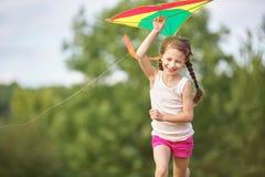 飞行风筝的女孩 免版税库存图片