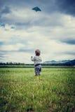 飞行风筝的小男孩 图库摄影