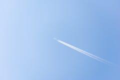 飞行高在与蒸气的天空的飞机落后 免版税库存照片