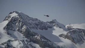 飞行高在高山山上的天空的直升机 股票录像