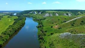 飞行鸟瞰图在绿色象草的岩石白垩小山、山和河的 股票录像