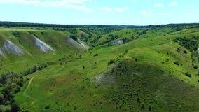 飞行鸟瞰图在绿色象草的岩石白垩小山和山的 股票录像