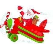 飞行他的圣诞节飞机的圣诞老人 库存照片