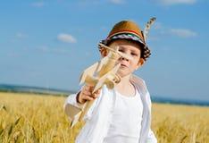飞行他的玩具双翼飞机的逗人喜爱的小男孩 免版税库存图片