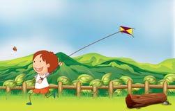 飞行他的风筝的男孩在桥梁 库存图片