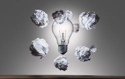 飞行arround电灯泡的被弄皱的纸球 图库摄影