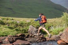 飞跃横跨岩石的运动远足者在河 免版税库存图片