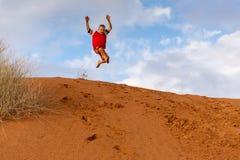 飞跃橙色沙丘的男孩有明亮的天空蔚蓝背景 免版税图库摄影