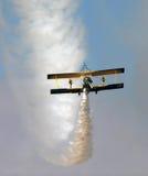 飞过站立在沙漠的一架双翼飞机的步行者 库存照片