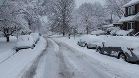 飞雪后果:冬天雪覆盖物汽车和路 免版税图库摄影