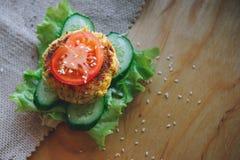素食三明治用鸡豆扁豆炸肉排、黄瓜、新鲜的莴苣和蕃茄 洒与芝麻籽 库存图片