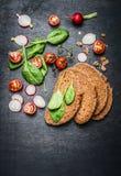 素食三明治的菜成份在黑暗的木背景 库存图片
