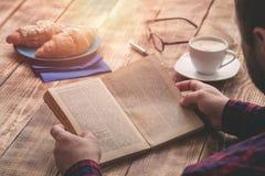 食人的早餐和阅读书关闭 免版税库存照片