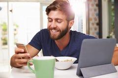 食人的早餐,使用数字式片剂和电话 库存照片
