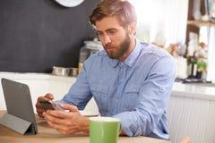 食人的早餐,使用数字式片剂和电话 免版税库存照片