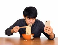 食人的面条和使用智能手机孤立 免版税库存照片