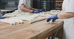 食品工业在准备面团和投入在架子的未来面包的面包店过程中装载是 股票录像