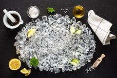 食品成分和被击碎的冰在黑桌上 免版税图库摄影