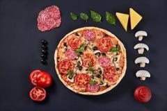 食品成分和香料烹调的和可口意大利薄饼在黑具体背景 免版税库存图片