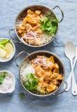 素食土豆和花椰菜咖喱用在咖喱盘的米在蓝色背景,顶视图 素食健康食物概念 库存图片
