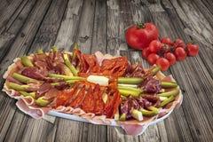食家与在老破裂的木庭院表上设置的束的开胃菜美味盘新鲜的成熟水多的蕃茄 库存照片