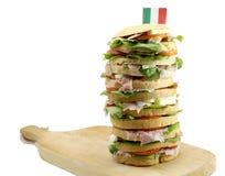 食家充塞了与蒜味咸腊肠乳酪和t许多层数的三明治  库存图片