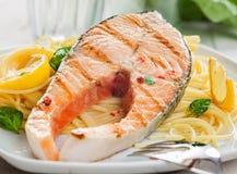 食家在扁面条面团的烤鲑鱼排 图库摄影