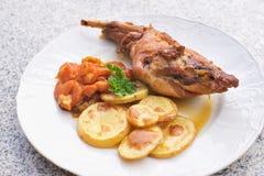 食家烤了兔子腿用给上釉的甜红萝卜,并且被烘烤的土豆在薄片choped 免版税图库摄影