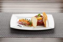 食家鞑靼,烤面包片和沙拉在板材 免版税库存照片