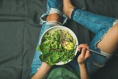 素食早餐碗用菠菜、芝麻菜、鲕梨、种子和新芽 免版税库存照片