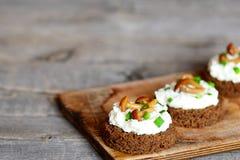 素食点心用软干酪和蘑菇在一个委员会在一张木桌上 库存照片