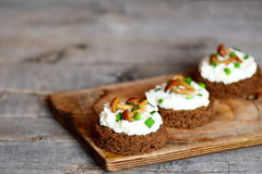 素食点心用软干酪和蘑菇在一个委员会在一张木桌上 库存图片