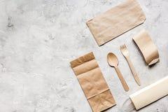 食物与纸袋的交付workdesk和扁平的餐具制表背景顶视图大模型 库存照片