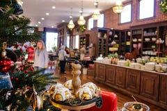 食物主题的圣诞树和显示与被弄脏的商店和人民有bokeh作用的 库存图片