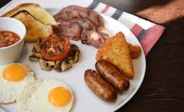 食物传统煮熟的英式早餐的摄影图象用煎蛋在板材的香肠蘑菇烟肉和豆 库存照片