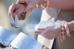 食物修士聘用 新郎给施舍食物传统泰国婚礼的一个和尚 手一会儿投入了食物奉献物  库存图片