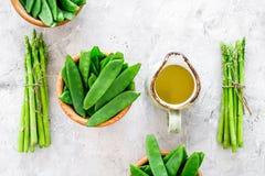 食物健康素食主义者 芦笋和豌豆在一个水罐油附近在灰色石背景顶视图 免版税库存照片