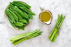 食物健康素食主义者 芦笋和豌豆在一个水罐油附近在灰色石背景顶视图 图库摄影