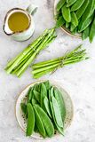 食物健康素食主义者 芦笋和豌豆在一个水罐油附近在灰色石背景顶视图 免版税库存图片