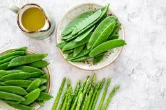 食物健康素食主义者 芦笋和豌豆在一个水罐油附近在灰色石背景顶视图copyspace 库存照片