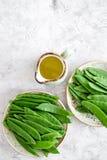 食物健康素食主义者 芦笋和豌豆在一个水罐油附近在灰色石背景顶视图copyspace 图库摄影