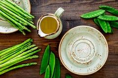 食物健康素食主义者 芦笋和豌豆在一个水罐油附近在黑暗的木背景顶视图 库存照片