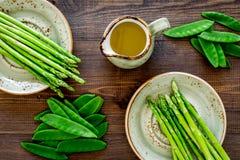 食物健康素食主义者 芦笋和豌豆在一个水罐油附近在黑暗的木背景顶视图 免版税库存图片