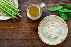 食物健康素食主义者 芦笋和豌豆在一个水罐油附近在黑暗的木背景顶视图copyspace 免版税库存照片